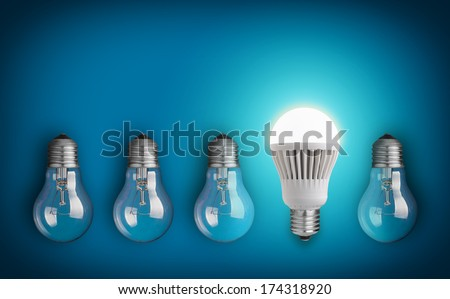 Idea concept with row of light bulbs and glowing LED bulb - stock photo