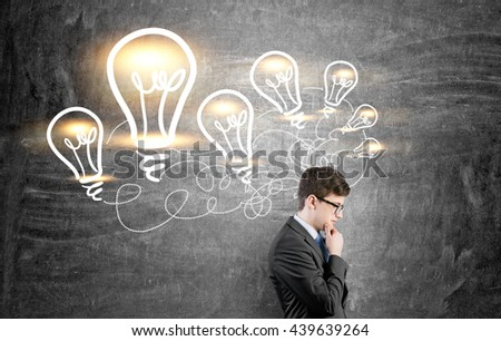 Idea concept with thoughtful businessman standing against chalkboard with illuminated lightbulb sketches - stock photo