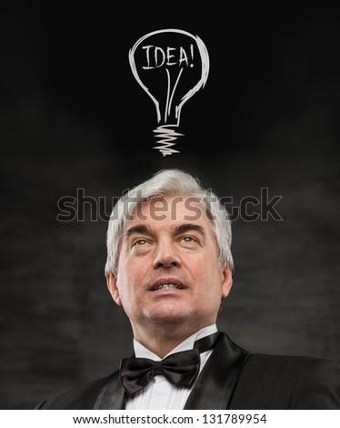 Idea man - brainstorming. Handsome mature man contemplating. Graphic lamp - symbol of new idea, overhead - stock photo