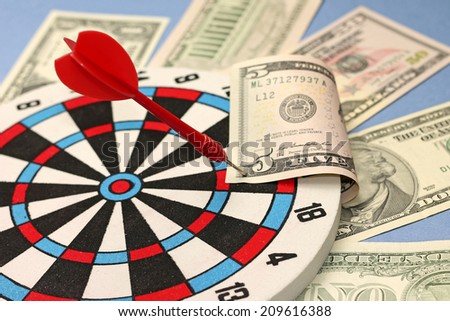 Idea of financial success - darts and dollars, close-up - stock photo
