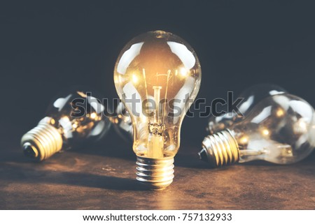 idea or light bulb on wooden table background