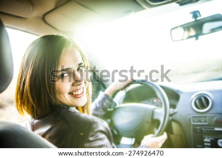 idea taxi driver talking to police companion companion who asks for directions right to drive Documents exam woman in car indoor keeps wheel turning around smiling looking at passengers in back seat - stock photo
