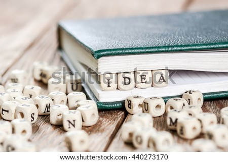 Idea word written on a wooden block in a book. On old wooden table.