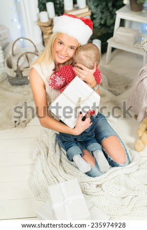 Ideal Christmas and New Year. Young and beautiful girl is sitting in festive Christmas decorated living room with her sun on her hands. She is wearing Santa Claus hat and sitting near fire place - stock photo