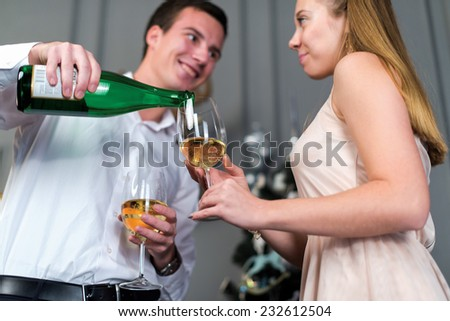 Ideal Christmas with champagne. Young and beautiful couple is standing in festive New Year living room and pouring champagne into glasses - stock photo