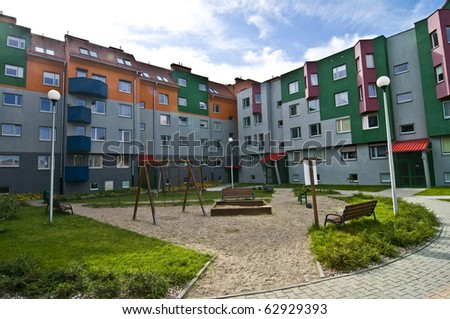 Ideal council estate, houses everyone would like to live in, with playground for kids, colorful, blue sky - stock photo