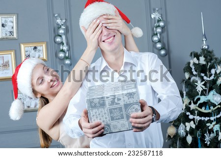 Ideal emotions before Christmas and New Year. Young and beautiful pair is having great time in festive New Year living room. Beautiful young girl is giving presents to her young and handsome husband - stock photo