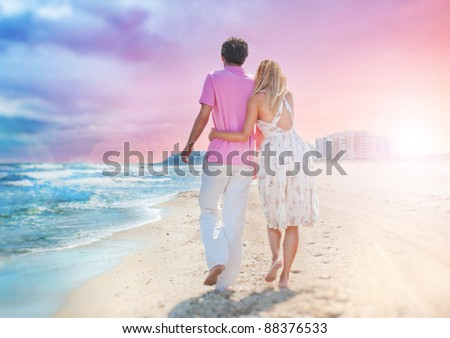 Idealistic poster for advertisement. Couple at the beach holding hands embracing and walking. Sunny day, bright colors. Photo from behind.  Europe, Spain, Costa Blanca - stock photo