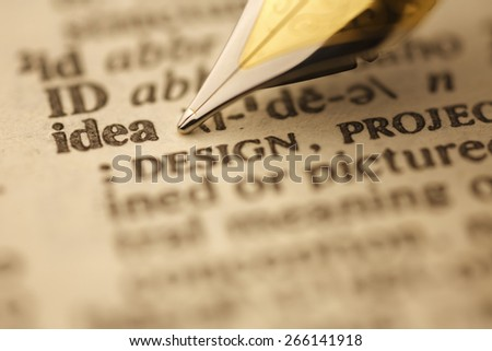Ideas pen nib pointing to the words in the dictionary, shot with very shallow depth of field, - stock photo