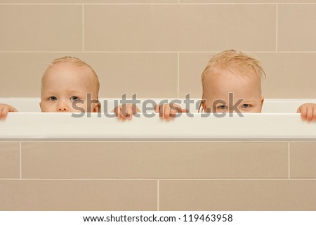 Identical twins toddlers peeking out from the bath. - stock photo