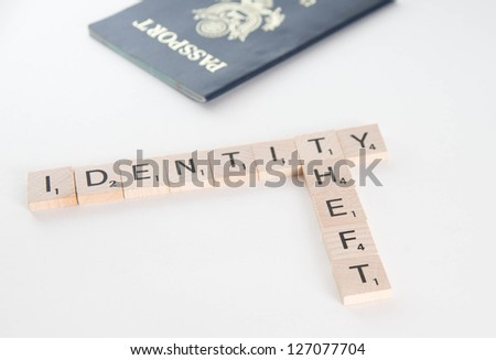 Identity theft spelled in Scrabble letters with US passport out of focus in the background. Isolated on white background. - stock photo