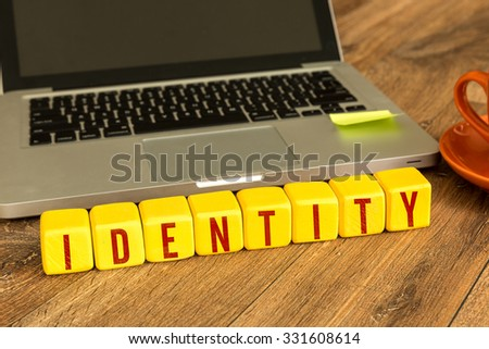Identity written on a wooden cube in front of a laptop - stock photo