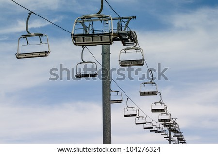 Idle lift chairs on cloudy blue sky. - stock photo