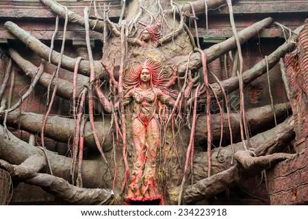 Idols of Hindu Goddess Durga and lord shiva carved out of a huge banyan tree - stock photo