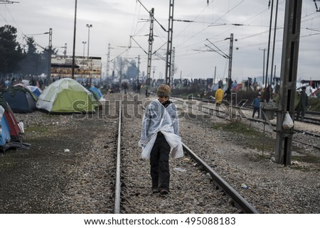 Idomeni, Greece - March 9, 2016. A refugee boy walks on the railway lines, in the refugee camp of Idomeni, in northern Greece. Around 10000 people were stranded at the Greek Macedonian border.