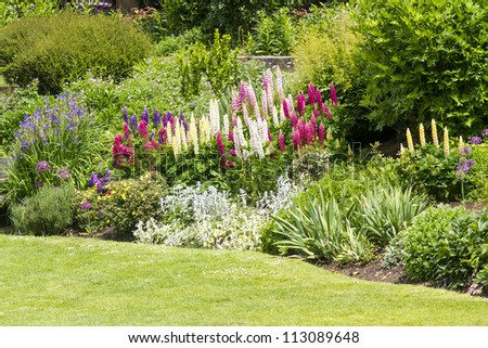 Idylic pretty English country formal garden, in full bloom. - stock photo