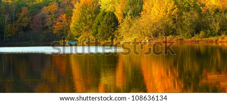 Idyllic fall foliage scene with reflections on lake with a wisp of wind ripples. - stock photo