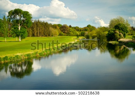 Idyllic golf course with reflection in the river - stock photo