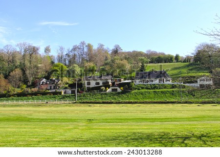Idyllic houses in picturesque valley field in Normandy, France - stock photo