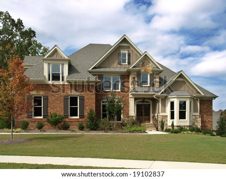 Idyllic Luxury Model Home with yard and blue cloud skies - stock photo