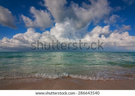 idyllic ocean beach view with sea sand water gentle waves and a dramatic blue sky with puffy clouds - stock photo