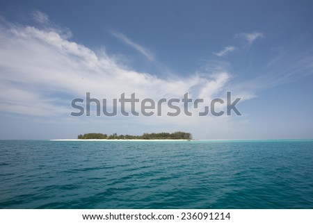 Idyllic paradise and dream holiday island in the Indian Ocean with turquoise and aqua ocean and a deep blue sea with wispy clouds surrounded by underwater coral reefs and white sandy beaches - stock photo