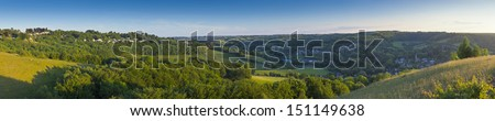 Idyllic rolling patchwork farmland with pretty wooded boundaries, lit in warm early evening sunshine in the heart of the Cotswolds, England, UK. Stitched panoramic image. - stock photo