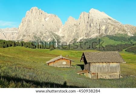 Idyllic scenery of rugged Sassolungo-Sassopiatto (Langkofel-Plattkofel) peaks & wooden barns on green meadows in Seiser Alm (Alpi di Siusi), Ortisei, National Park Dolomites, South Tyrol, Italy Europe - stock photo