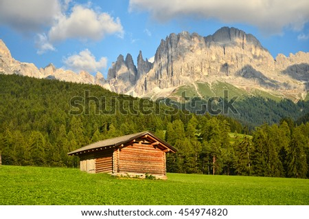 Idyllic scenery of rugged Sassolungo-Sassopiatto (Langkofel-Plattkofel) peaks & wooden barns on green meadows in Seiser Alm (Alpi di Siusi), Ortisei, National Park Dolomites, South Tyrol Italy Europe - stock photo