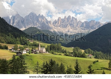 Idyllic scenery of Val di Funes in summer season with rugged peaks of Odle mountain range in background & a church in Village Santa Maddalena in the green grassy valley in Dolomiti, South Tyrol, Italy - stock photo