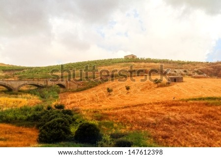 Idyllic Sicilian Summer Landscape with old huts, an old aqueduct like railway and a man, working in the fields - stock photo