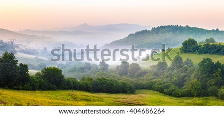 idyllic summer landscape with cold morning fog on hillside in mountainous rural area before sunrise - stock photo