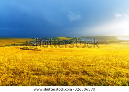 Idyllic summer landscape with lake and green and yellow meadow. Central Europe.
