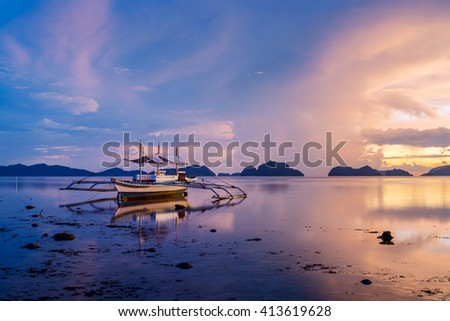 Idyllic sunset with traditional Banca boat at El Nido, Palawan, Philippines. - stock photo