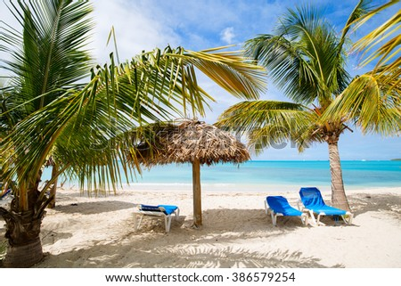 Idyllic tropical beach at Antigua island in Caribbean with white sand, turquoise ocean water, palm trees and blue sky - stock photo