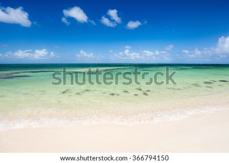 Idyllic tropical beach on Barbuda island in Caribbean with white sand, turquoise ocean water and blue sky - stock photo