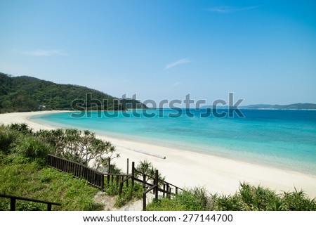 Idyllic tropical beach paradise blue lagoon full of clear water and healthy coral on stunning white sand beach with greenery. - stock photo