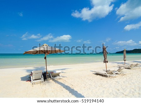 Idyllic tropical beach with relaxing chais and umbrella in sunny day
