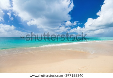 Idyllic tropical beach with white sand, turquoise ocean water and blue sky at Antigua island in Caribbean - stock photo