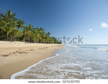 Idyllic tropical getaway at Mission Beach, Queensland, Australia with gentle surf lapping golden sand fringed with lush vegetation and palm trees