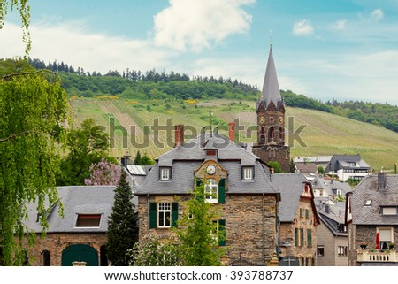 idyllic village Lieser, beside mosel river at springtime, with hillside vineyards