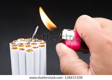 igniting a bundle of cigarettes with tinder - stock photo