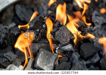 Igniting charcoal for a barbecue with bright orange flames