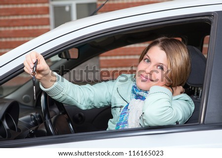 Ignition key in hand of female sitting in car