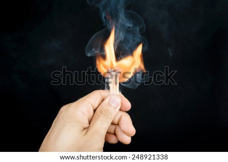 Ignition of a match, with smoke on dark background. - stock photo