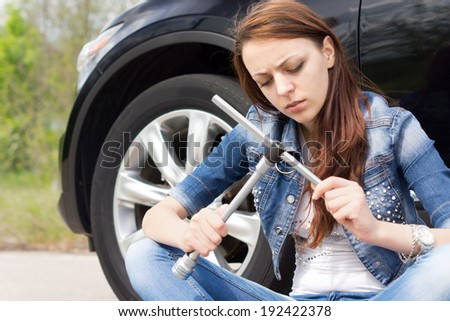 Ignorant woman frowning at a wheel spanner as she sits on the road alongside her car following a breakdown waiting for assistance - stock photo