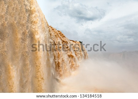 Iguazu falls, one of the new seven wonders of nature. UNESCO World Heritage site. View from the brazilian side during rains season, with water on terrain colors. - stock photo