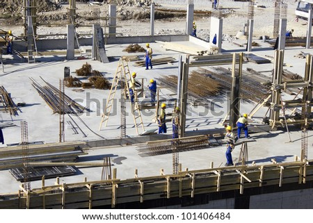 Iindustrial workers with hardhats and uniform  at construction site during the erection of multistory building - stock photo