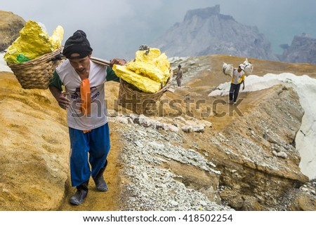 Ijen Crater, Java, Indonesia - May 25: Sulfur miner carrying sulfur-laden baskets at Kawah Ijen volcano in East Java, Indonesia.  - stock photo