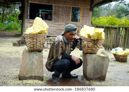IJEN, INDONESIA - APR 06: Worker carries sulfur from crater inside on April 06, 2014 in Ijen Volcano, Indonesia. They will be paid in cash with the price of Rp700 per kg sulfur brought by employer - stock photo